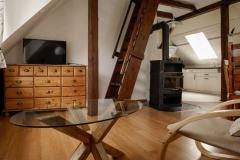 Wohnzimmer mit Kaminofen und Aufgang zum Dachspitz -  Foto: A. Declair